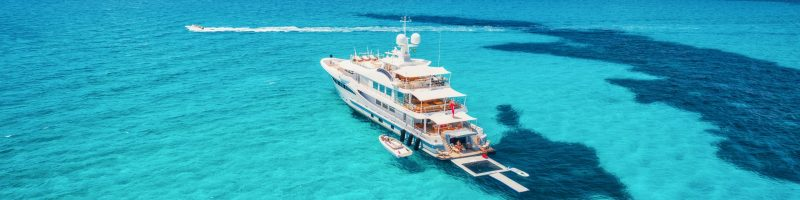 Yacht on the azure seashore in balearic islands. Aerial view of floating boat with people in transparent sea at sunny day in summer. Top view from drone. Seascape with luxury yachts in motion in bay